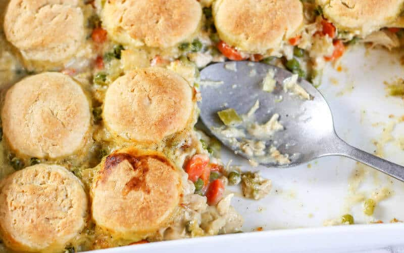 chicken pot pie in white casserole dish with silver spoon and biscuit top