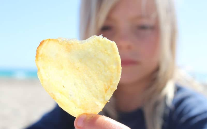 girl holding up chip at the beach