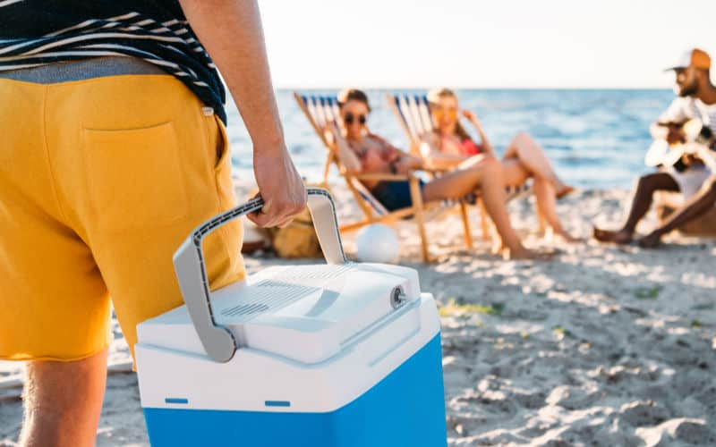 man carrying a cooler with beach foods