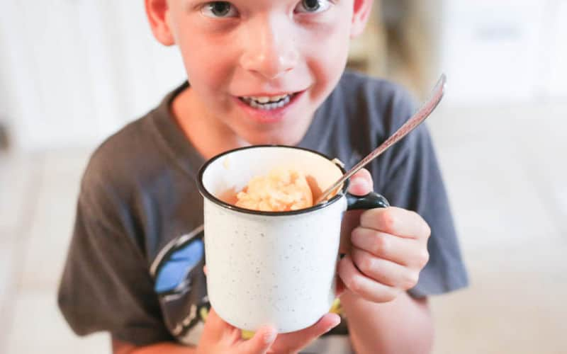 child holding white mug filled with orange pineapple churned ice cream