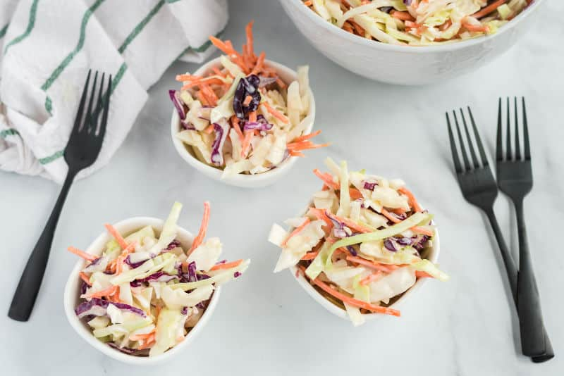 southern traditional cole slaw in bowls with black forks