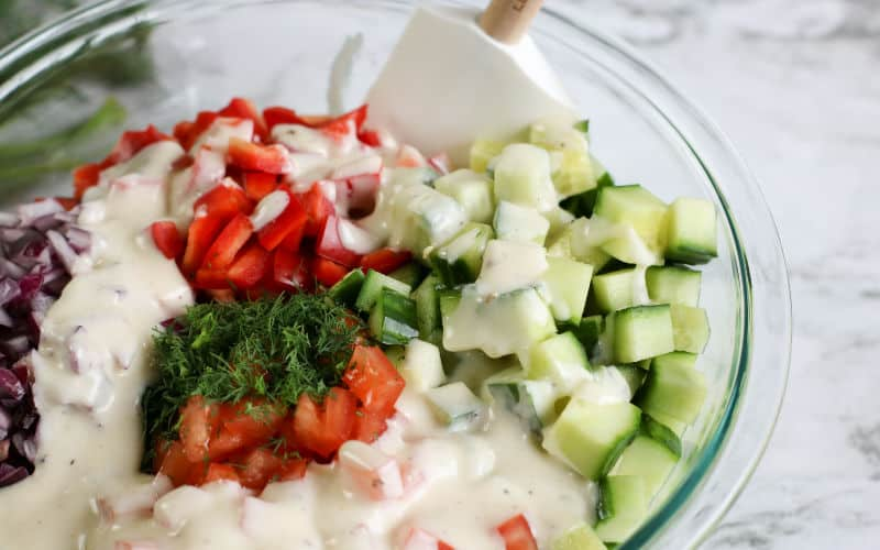 mayo, cucumber, pepper, tomatoes, dill, and onions for a creamy cucumber sald
