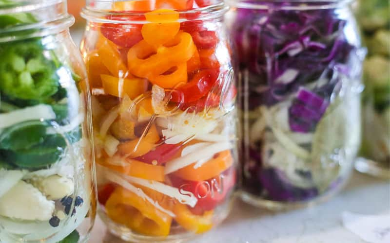 sweet peppers that are sliced, with pickled jalapenos and pickled cabbage