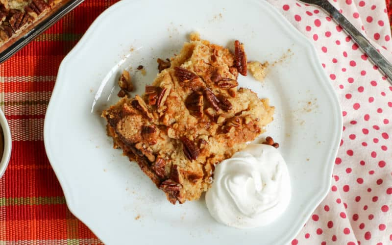 pumpkin pecan cobbler on a white plate with cream
