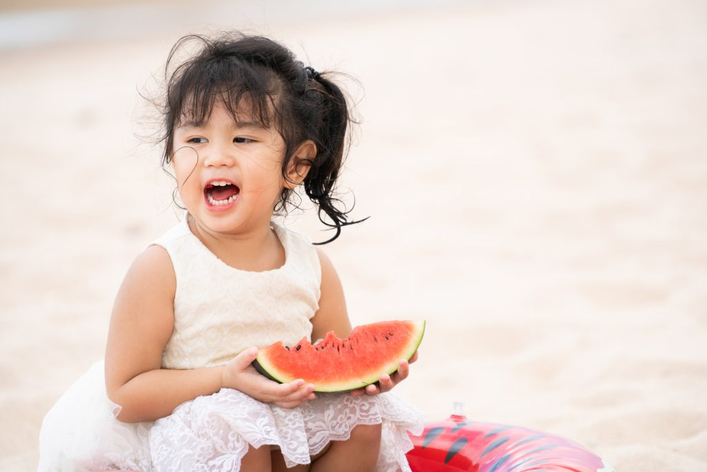 little girl eating watermelon at the beach